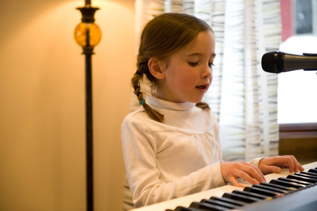 girl playing the piano and singing